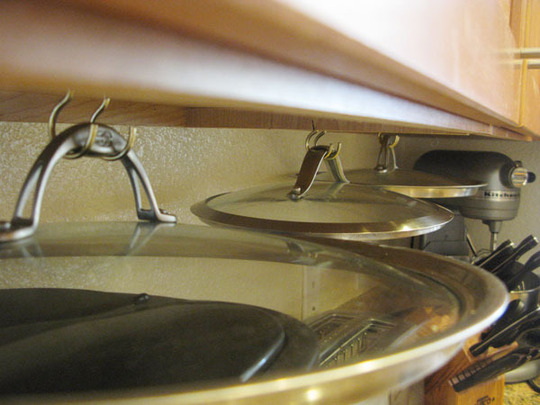 Hanging Pot Lids Under Cabinets Helps To Save Space